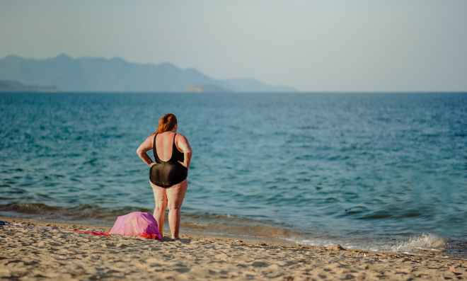 photography of a woman in black swimsuit standing on the seashore