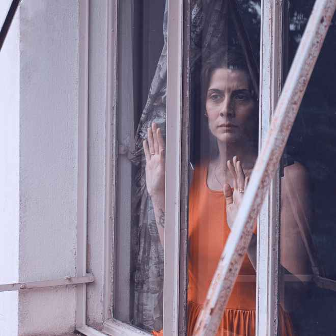 woman staring through window