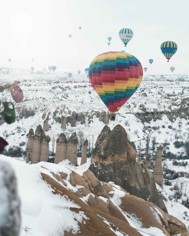 hot air balloons over snow covered mountain