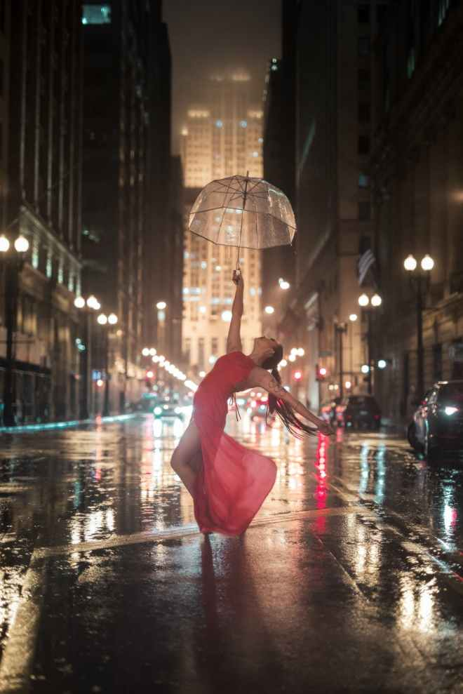 woman holding umbrella dancing in the middle of the road near cars and buildings